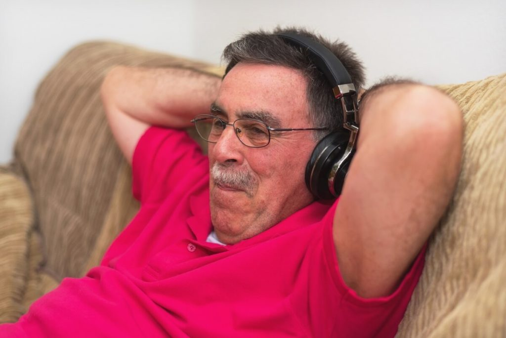 A man on a couch listening through headphones.