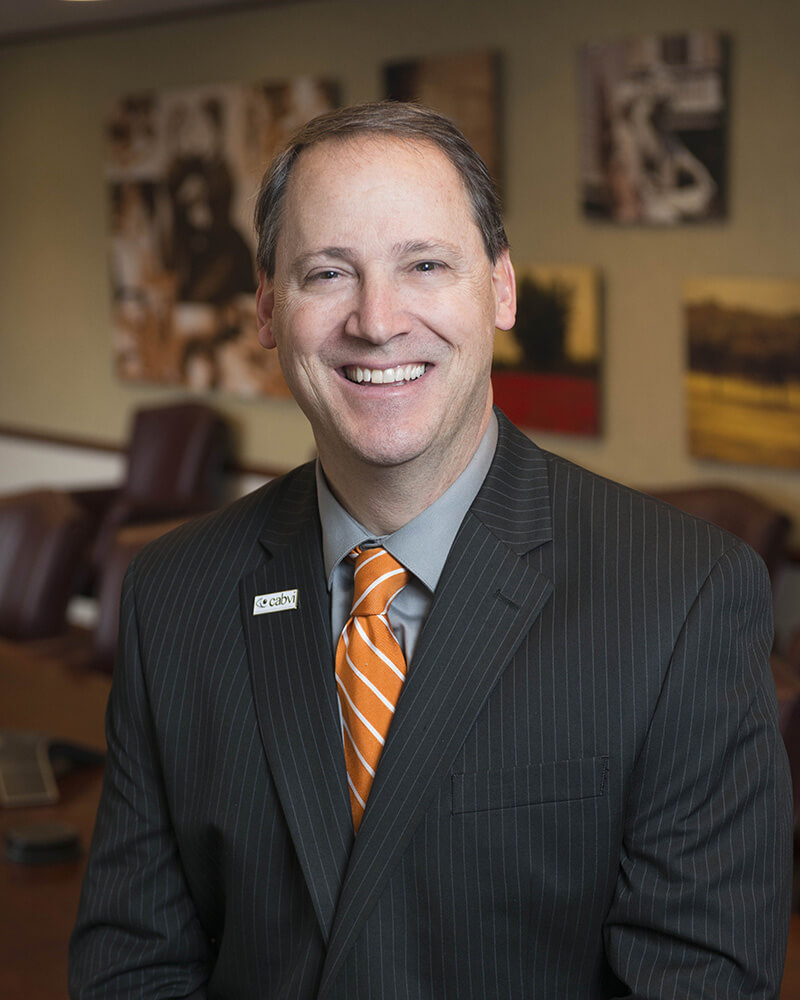 Senior Vice President of Manufacturing and Public & Government Affairs, Dennis Webster. He is wearing a grey shirt, a orange and white tie, and a grey suit.