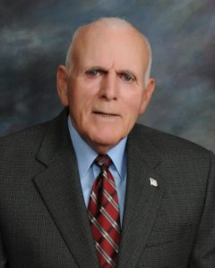 Board member, Richard Evans. He is wearing a grey blazer with a blue shirt and a red and grey tie. There is a United States pin on his blazer.