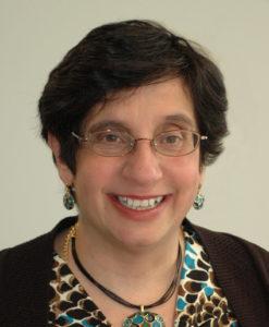 Board member, Joanne Joseph. She is wearing a brown cardigan over a brown shirt.