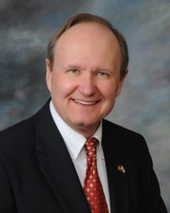 Board member, Thomas P. Webb. He is wearing a black blazer with a white shirt and a red and yellow tie.