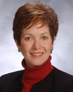 Board secretary, Margaret G. Brown. She is wearing a red turtleneck,