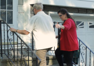 A woman helps a man walk up the front steps of a house.