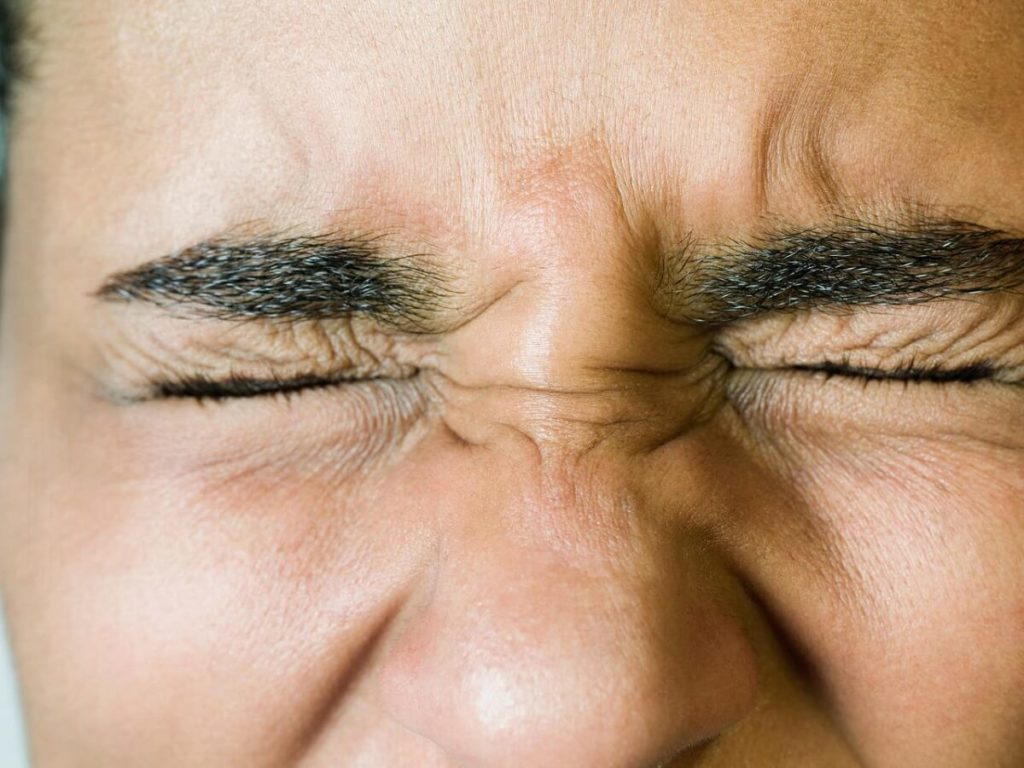 Closeup of someone squinting their eyes shut tight.