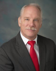 CABVI board member, Michael J. Misiaszek. He is wearing a grey blazer with a white shirt and red tie.