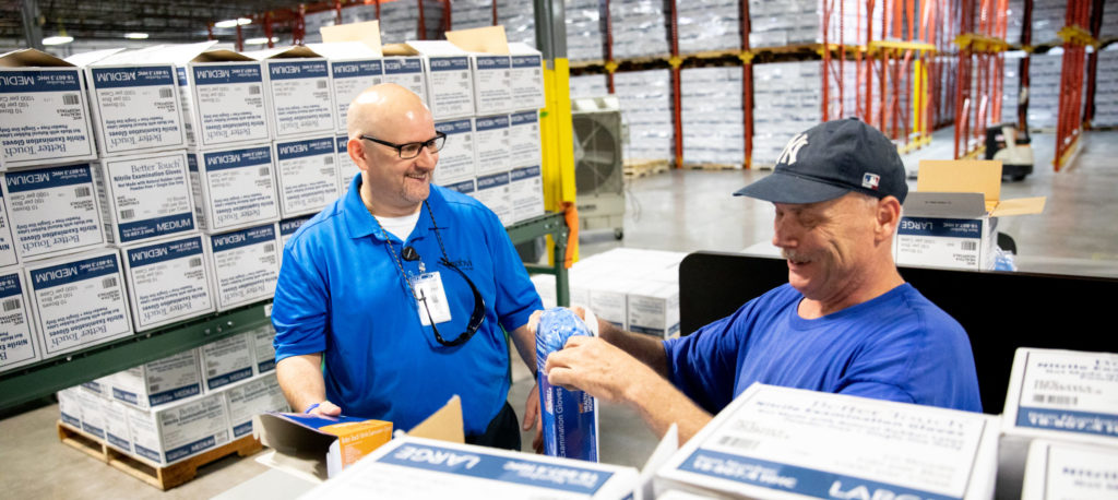 A visually impaired glove packager talking to general manager, Ron Baron, on the glove line.
