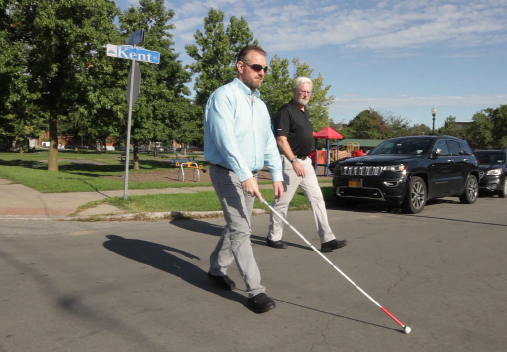 A visually impaired man using a white cane to cross the street. A sighted guide is walking next to the visually impaired man.