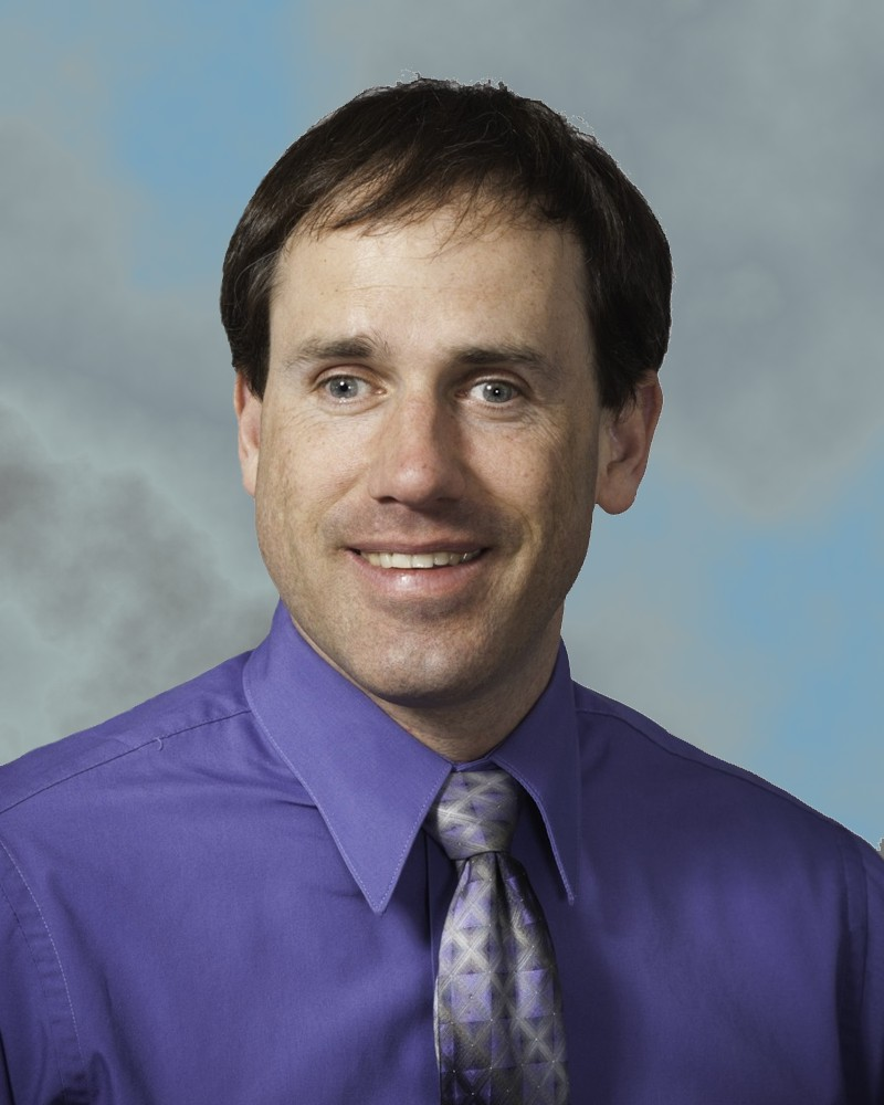 Shawn Kelly. He is wearing a purple shirt with a grey and purple tie.