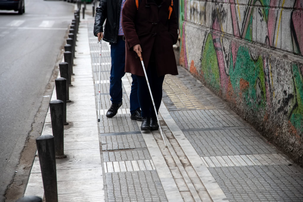 A visually impaired man and women using their white canes to track the path of tactile paving.