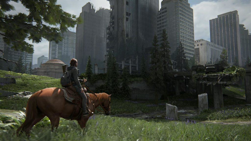 """A screenshot of the video game """"The Last of Us Part 2"""". Ellie, the main character, is riding a horse into a abandoned city."""