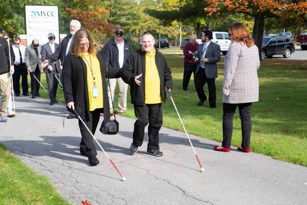 Several visually impaired people walking around using white canes.