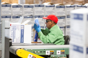 A material handler putting gloves into a box.