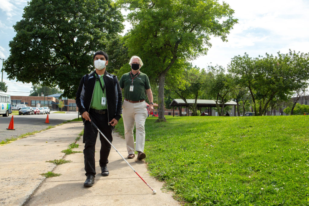 A visually impaired man using a white cane with a sighted guide behind him.