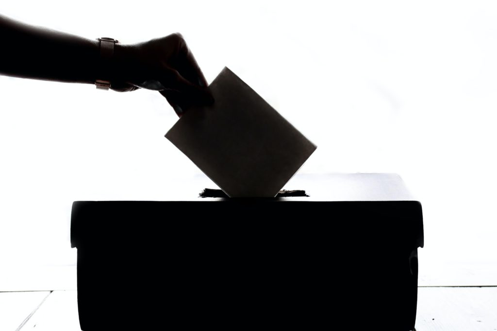 A hand putting a piece of paper in a ballot box.