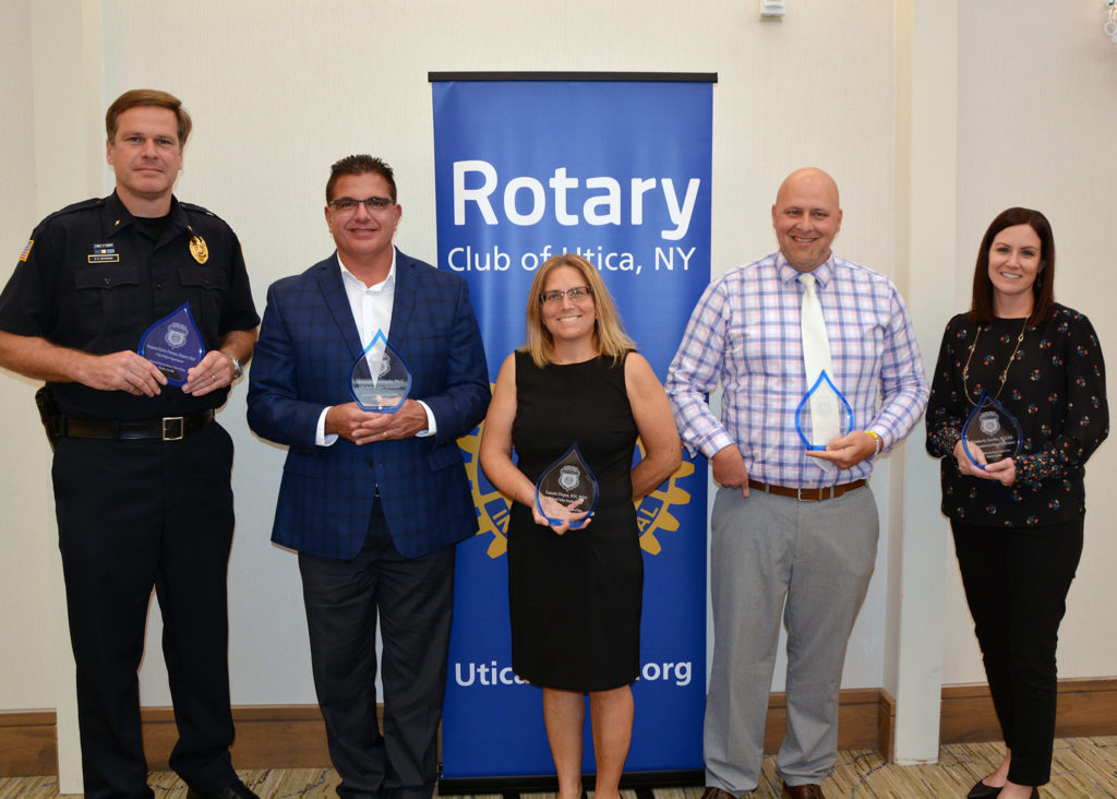 A group of people standing with awards in front of a Rotary banner