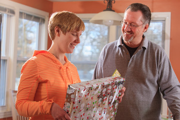 A visually impaired girl is opening a gift and her dad is standing next to her