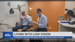 A doctor and a patient are in a low vision exam room with orange walls