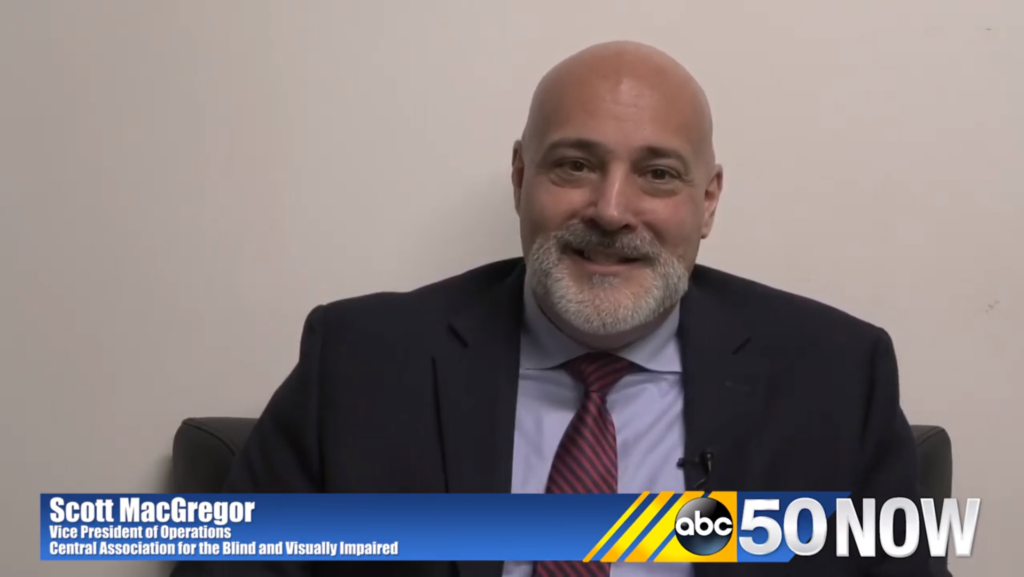 Scott MacGregor smiling on camera with the logo ABC50